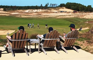 Golfers relax at a refreshment area called Craig's Porch at the Sand Valley Golf Resort.
