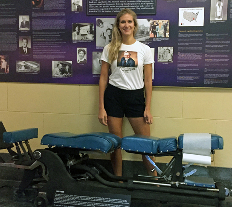 Amanda Berkley poses with her grandfather's adjusting table displayed at Palmer College of Chiropractic in Davenport, Iowa, where she graduates in February. Photo courtesy of Amanda Berkley.