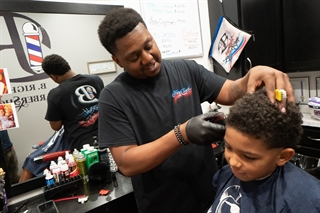 Jason Boatright cuts the hair of his stepson, Keegan Hill, 10, at his B. Right Barbershop in Sun Prairie. Wisconsin licensure reforms enabled Boatright to open his shop soon after he earned his barber's license. Photo by John Maniaci.