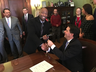 Barber Albert Walker shakes the governor's hand at the Nov. 27 bill signing. Licensing regulations had prevented Albert Walker from managing his own shop.