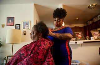 Sharon Hudson does the hair of Suzanne Turner at the client's home in Milwaukee. Photo by Darren Hauck.